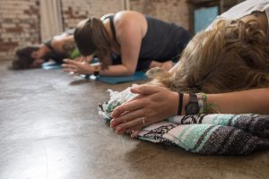 Girl with folded prayer hands in yoga class