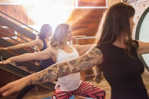 Three women do warrior two yoga pose