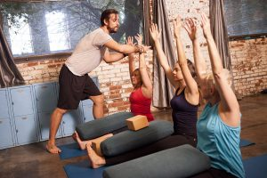 Yoga instructor offering hands-on adjustment to class