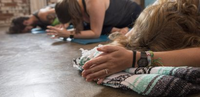 Woman with folded prayer hands uses yoga prop in class