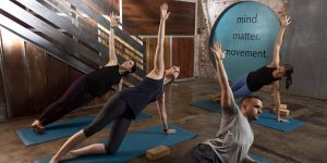 Man and two women take yoga class and stretch