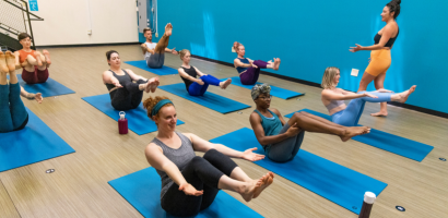 Yoga class holding boat pose